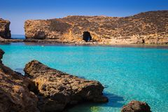 Comino, Malta - Beautiful azure sea water at the famous Bluw Lagoon of Comino. With snorkeling tourists enjoying the summer sunshine Stock Image