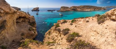 Comino, Malta - The beautiful Blue Lagoon with turquoise clear sea water, yachts and snorkeling tourists. On a sunny summer day with the island of Gozo at Royalty Free Stock Image