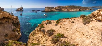 Comino, Malta - The beautiful Blue Lagoon with turquoise clear sea water, yachts and snorkeling tourists. On a sunny summer day with the island of Gozo at Royalty Free Stock Photos