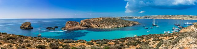 Comino, Malta - Panoramic skyline view of the famous and beautiful Blue Lagoon on the island of Comino. With sailboats, traditional Luzzu boats and tourists stock image