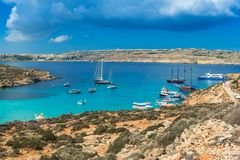 Comino, Malta - Panoramic skyline view of the famous and beautiful Blue Lagoon on the island of Comino. With sailboats, traditional Luzzu boats and tourists Royalty Free Stock Photos