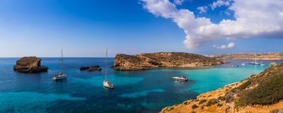 Comino, Malta - Panoramic skyline view of the famous and beautiful Blue Lagoon on the island of Comino with sailboats. Traditional Luzzu boats and tourists Royalty Free Stock Photos