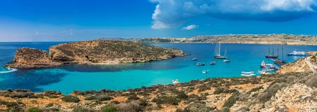 Comino, Malta - Panoramic skyline view of the famous and beautiful Blue Lagoon on the island of Comino with sailboats. Traditional Luzzu boats and tourists Stock Image