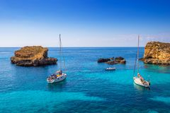 Comino, Malta - Sailing boats at the beautiful Blue Lagoon at Comino Island. With turquoise clear sea water, blue sky and rocks in the water Stock Photos