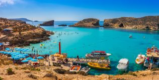 Comino, Malta - Tourists crowd at Blue Lagoon to enjoy the clear turquoise water. On a sunny summer day with clear blue sky and boats on Comino island, Malta Stock Photography