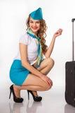 A comissária de bordo bonita guarda a bagagem foto de stock