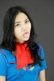 Comissária de bordo de ar asiática que pica para fora a língua para a câmera Foto de Stock Royalty Free