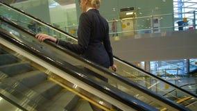 A comissária de bordo loura monta acima na escada rolante com a mala de viagem no aeroporto vídeos de arquivo
