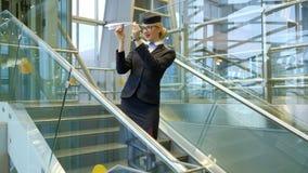 Comissária de bordo loura que está nas escadas que fazem a brinquedo o plano de papel no salão filme