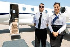 Comissária de bordo And Pilot Standing contra o jato privado Imagens de Stock
