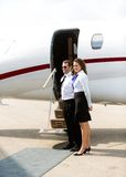 Comissária de bordo And Pilot Standing contra o jato privado Imagem de Stock