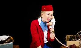 Comissária de bordo retro Preparing para o trabalho e fala da linha aérea no T Fotografia de Stock Royalty Free