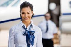 Comissárias de bordo bonitas que sorriem com piloto And Private fotografia de stock royalty free
