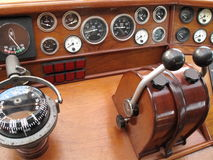In command: ship's bridge. Control and command center/bridge for large brigantine, showing instrumentation, lights, dials, gauges, compass, and forward/reverse Royalty Free Stock Photos