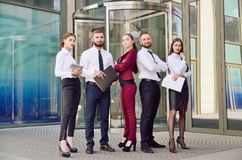 Command. Young office workers on the background of a multi-storey glass building. Five managers. Teamwork. Office. A group stock images