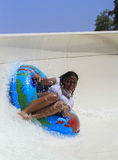 Commande gaie noire de fille avec le tube sur la glissière transportante par radeau Photos libres de droits