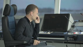 Commander is using the portable radio to give orders airport employees. Dispatcher controls the air-traffic in the control tower in airport. Commander is using stock footage
