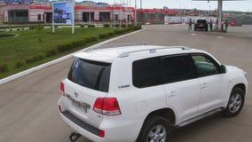 Commandes blanches de voiture de vue aérienne pour réapprovisionner en combustible la station clips vidéos