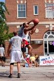 Commandes de jeune homme au panier dans le tournoi extérieur de basket-ball de rue Photographie stock libre de droits