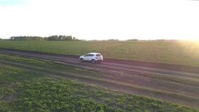 Commandes de voiture le long de la route moulue après des champs au coucher du soleil lumineux clips vidéos
