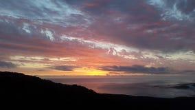 Comme le soleil se couche et les faisceaux lumineux en avant au-dessus de l'océan Photos stock