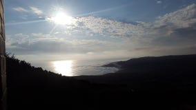 Comme le soleil se couche et les faisceaux lumineux en avant au-dessus de l'océan Images libres de droits