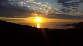 Comme le soleil se couche et les faisceaux lumineux en avant au-dessus de l'océan Image libre de droits
