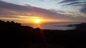 Comme le soleil se couche et les faisceaux lumineux en avant au-dessus de l'océan Photos libres de droits