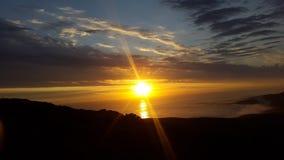 Comme le soleil se couche et les faisceaux lumineux en avant au-dessus de l'océan Photo libre de droits