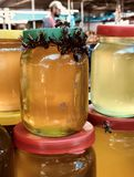 COMME UNE ABEILLE AU MIEL - un essaim des abeilles est attiré à une pile de pots de miel Photo stock