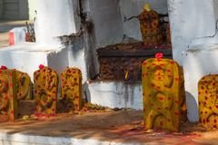 Group of yellow monuments with red dots in Shiva temple, Tamil Nadu, India. Commemorating the dead in ancient temple. Group of yellow monuments with red dots in stock image