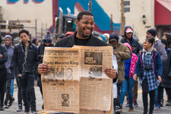 Commemorating Martin Luther King, Jr. Washington, DC - January 16, 2017: Man holds vintage newspaper during the Martin Luther King, Jr. Day Peace Walk and Royalty Free Stock Photo