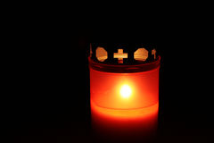 Commemoration. Votive candle on All Saints' Day shining warm out of the dark royalty free stock photos