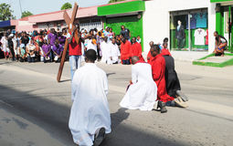 COMMEMORATION OF THE PASSION OF THE CHRIST. Image of Christian African Catholics with priests putting knees to commemorate the passion of Christ with fervor royalty free stock images