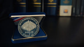 Commemorative 1 dollar silver coin on a black table with binders and books in the background. Numismatic Scene stock image