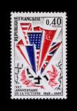 Commemorative stamp of the victory of 1945. Vintage French stamp depicting the Allied flags American, Russian, English and French stomping on the Nazi flag to Stock Photos