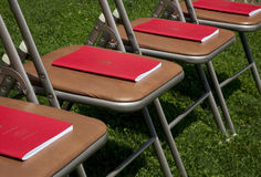 Commencement Programs on Chairs. A section of a  row of chairs set up at college commencement exercises. Each chair has a neatly-placed red commencement program Stock Images