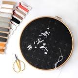 Commencer de la broderie sur la toile noire par les fils de laine Hôte photo stock