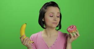 Commencer la consommation saine Dites non ? la nourriture industrielle Beignet ou banane bien choisi ? manger banque de vidéos