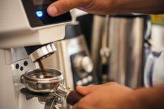 Commencer par la meilleure broyeur de café Le barman fait l'expresso en café Haricots de morcellement de barman avec la machine d photo libre de droits