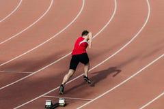 Commencez dans 400 mètres au coureur d'homme de stade Image stock