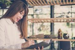 Commencez le travail de femme en café l'étudiante écrivent la note dans le noteb photo stock