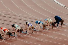 Commencez les sprinters féminins dans 100 mètres de fonctionnement Photos libres de droits