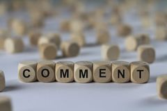 Comment - cube with letters, sign with wooden cubes. Comment - wooden cubes with the inscription `cube with letters, sign with wooden cubes`. This image belongs Royalty Free Stock Photo