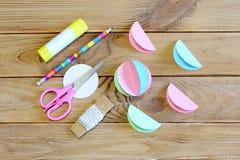 Comment faire un ornement de boule de Noël de papier coloré opération Collez les cercles de papier pliés dans la moitié, ciseaux, Photos stock