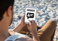Comment text and chat graphic on tablet screen with mans hands Stock Photo