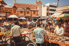 Commerçants des ananas et des fruits tropicaux parlant avec des clients au marché en plein air Photo stock