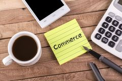 Commerce word on memo. With pen , coffee , mobile and calculator on wooden table Stock Photography
