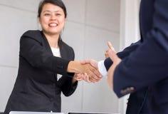 Commerciële Aziatische teammensen die handen na het eindigen schudden omhoog samenkomend in conferentieruimte stock foto