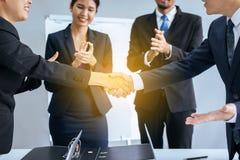 Commerciële Aziatische teammensen die handen na het eindigen schudden omhoog samenkomend in conferentieruimte royalty-vrije stock afbeelding